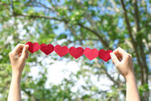Female hands with chain of paper hearts — Stock Photo