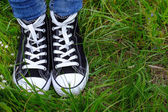 Female feet in gumshoes on green grass — Stock Photo