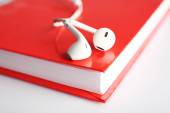 Earphones and book on table — Stock Photo