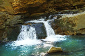 Water flowing on rocks in park — Stock Photo