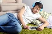 Knappe jongeman liggen op tapijt en luisteren naar muziek in kamer — Stockfoto