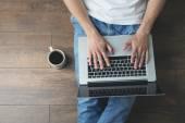 Młody człowiek siedział na podłodze z laptopa i filiżankę kawy w pokoju — Zdjęcie stockowe