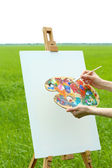 Female hand holding palette and easel with canvas in green field — Stock Photo
