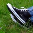 Female feet in gumshoes on green grass background — Stock Photo #75218769