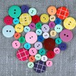 Colorful buttons in shape of heart on sackcloth background — Stock Photo #75218929