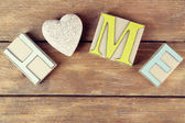 Decorative letters forming word HOME with decorative heart on wooden background — Stock Photo
