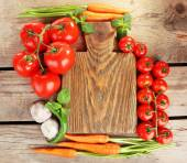 Fresh vegetables with cutting board on wooden table, top view — Stock Photo