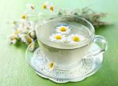Cup of chamomile tea with chamomile flowers and tasty muffins — Stock Photo
