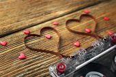 Audio cassette with magnetic tape in shape of hearts on wooden background — Stock Photo