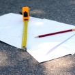 Building roulette and pencil on white sheets of paper, outdoors — Stock Photo #75300845