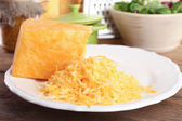 Grated cheese on wooden table in kitchen, closeup — Stock Photo