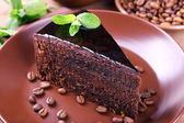 Delicious chocolate cake with mint on plate on table close up — Stock Photo