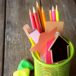 Colorful pencils with paper notes in metal stand on wooden table background — Stock Photo #75489707