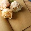 Fresh roses on old notebook, on wooden table background — Stock Photo #75498975