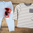 Clothes for baby boy on wooden background — Stock Photo #75490619