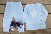Clothes for baby boy on wooden background — Stock Photo