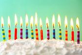 Geburtstagstorte mit Kerzen auf farbigem Hintergrund — Stockfoto