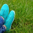 Female feet in gumshoes on green grass background — Stock Photo #75502757