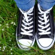 Female feet in gumshoes on green grass background — Stock Photo #75503053