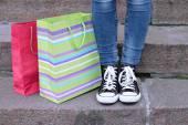 Piedi femminili in gumshoes vicino a shopping bag su scale di pietra — Foto Stock