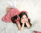 Beautiful little girl listening to music in room — Stock Photo