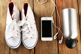 Sneakers and earphones on wooden table, top view — Stock Photo