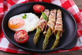 Dish of asparagus with eggs and bacon in pan on table, closeup — Stock Photo