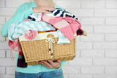Woman holding basket with heap of different clothes — Stock Photo