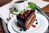 Delicious chocolate cake with berries and cup of coffee — Stock Photo