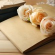 Fresh roses on old notebook, on wooden table background — Stock Photo #75755955
