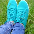 Female feet in gumshoes on green grass — Stock Photo #75759103