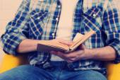 Young man reading book, close-up, on light background — Stock Photo