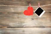 Bright heart and photo paper hanging on rope on wooden background — Stockfoto