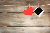 Bright heart and photo paper hanging on rope on wooden background — Stock Photo