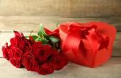 Boîte de cadeau de Saint Valentin avec des roses rouges sur la vieille table en bois en forme de coeur — Photo