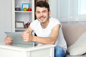 Handsome young man sitting on sofa and using tablet in room — Stock Photo