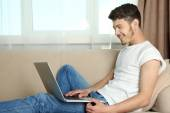 Handsome young man sitting on sofa and using laptop in room — Stock Photo