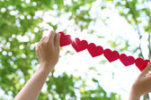 Female hands with chain of paper hearts over nature background — Stock Photo