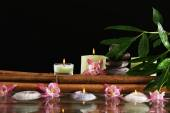 Spa still life with flowers and candlelight on black background — Stock Photo