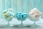 Set of candies in glassware on wooden background — Stock Photo