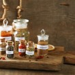 Assortment of spices in glass bottles on cutting board, on wooden background — Stockfoto #75811385
