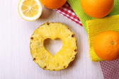 Pineapple slice with cut in shape of heart and different fruits on table close up — Stock Photo