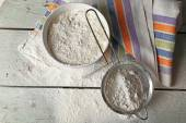 Sifting flour through sieve on wooden table, top view — Stock Photo