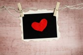 Bright heart on photo paper hanging on rope — Stock Photo
