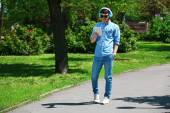 Man walking with headphones in park — Stock Photo