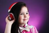 Beautiful little girl listening to music on colour background — Stock Photo