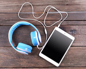 Headphones with tablet on wooden background — Stock Photo