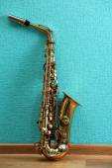 Saxophone on turquoise wallpaper background — Stock Photo