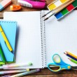 Notebook and bright school stationery on old wooden table — Stock Photo #76216057