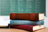 Stack of books on desk, on blackboard background — Stock Photo